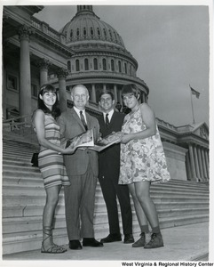 Congressman Arch A. Moore, Jr. standing on the steps of the Capitol with two Swedish women.