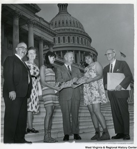 Congressman Arch A. Moore, Jr. on the steps of the Capitol with two Swedish women. Three other unidentified people are standing with them.