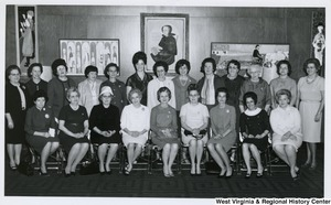 An unidentified group of women sitting. There are four paintings hanging on the wall behind them.