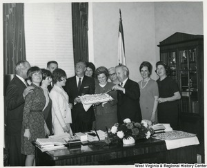 Congressman Arch A. Moore, Jr. pointing to his birthday cake with a knife. The cake is being held by Mrs. Shelley Moore, and an unidentified man. Moore is surrounded by a group of people.