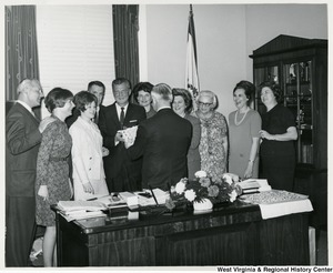 Congressman Arch A. Moore, Jr. (with his back to the camera) looking at his birthday cake. He is surrounded by his wife, Shelley, and a large group of people.