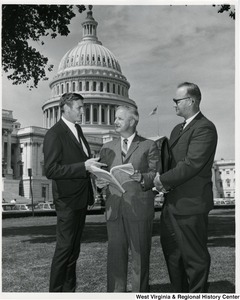 Congressman Arch A. Moore, Jr. (center) standing on the lawn of the Capitol with two unidentified men. Moore is showing the two men the Congressional Record.