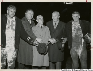 Three unidentified men standing with two mud covered football players from the Hampshire Trojans Football team (Romney, W.Va.). They are all shaking hands.