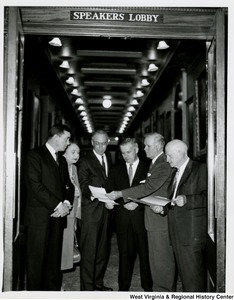 Congressman Arch A. Moore, Jr. with the  West Virginia delegation going over a document. They are standing in the doorway of the Speakers Lobby at the Capitol. From left to right: John M. Slack Jr. (D); Elizabeth Kee (D); Ken Hechler (D); Arch A. Moore, Jr. (R); Cleveland M. Bailey (D); and Harley Orrin Staggers (D).