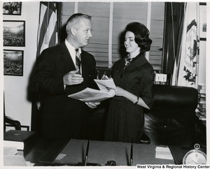 Congressman Arch A. Moore, Jr. discussing a document with an unidentified woman in his office.