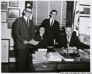 Congressman Arch A. Moore, Jr. seated at his desk with three unidentified people.