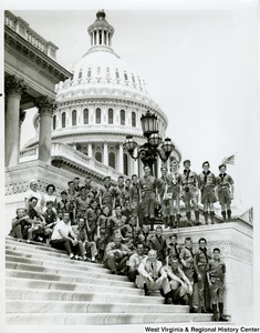 Congressman Arch A. Moore, Jr. sitting on the steps of the Capitol with a group of Boy Scouts.