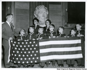 Congressman Arch A. Moore, Jr. holding the American Flag with a group of Boy Scouts in the National Statuary Hall at the Capitol.