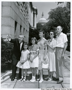 Congressman Arch A. Moore, Jr. pointing out something to an unidentified family of five.