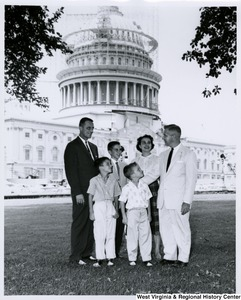 Congressman Arch A. Moore, Jr. standing on the lawn of the Capitol with an unidentified family of five. The Capitol dome is under construction in the background.