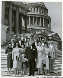 Congressman Arch A. Moore, Jr. standing on the steps of the Capitol with a unidentified group of men and women.