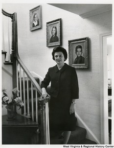 Mrs. Shelley Moore standing in the stairwell of their home. Pictures of her three children are on the wall behind her.