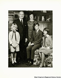 Congressman Arch A. Moore, Jr. standing with his wife, Shelley, and youngest daughter Lucy. Their oldest daughter, Shelley, is seated in a chair beside them with Kim (Arch III), sitting on the arm of the chair.