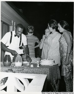 An unidentified man is placing a cut piece of cake on a plate while four women wait.