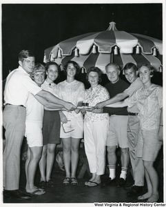 Congressman Arch A. Moore, Jr. (right of center)  and his wife Shelley (center) holding onto a plate with a bowl on it with six unidentified young people, likely interns.