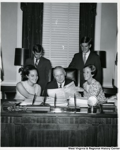 Congressman Arch A. Moore, Jr. sitting at his desk showing two women and two men, probably interns, the Congressional Record.
