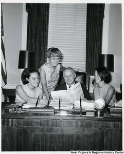 Congressman Arch A. Moore, Jr. sitting at his desk showing three unidentified women, probably interns, the Congressional Record.