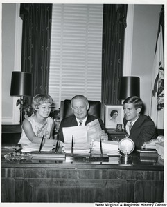 Congressman Arch A. Moore, Jr. seated at his desk showing an unidentified man and woman, probably interns, the Congressional Record.