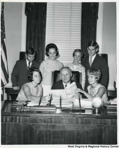 Congressman Arch A. Moore, Jr. sitting at his desk showing six unidentified people, probably interns, the Congressional Record.