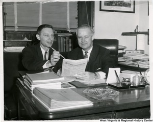 Congressman Arch A. Moore, Jr. seated at his desk discussing the Congressional Record with an unidentified man.