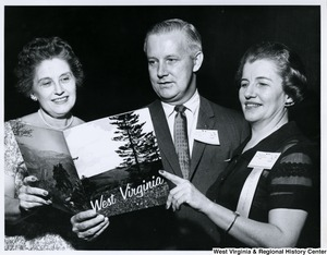 Congressman Arch A. Moore, Jr. with two unidentified women looking at a book of West Virginia. Moore and the woman on the right are wearing Republican National Convention 1960 badges.