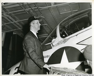 Congressman Arch A. Moore, Jr. standing on a stool inspecting an airplane on board the U.S.S. Franklin D. Roosevelt.